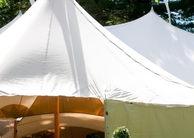 a large white wedding tent set up outside for a catered event